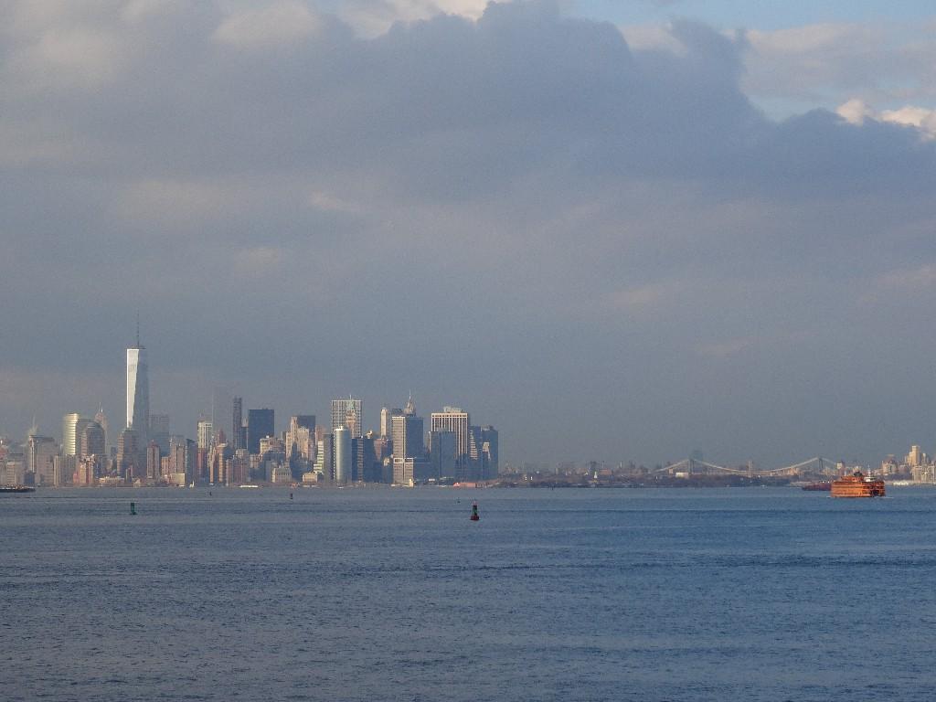 Widok na Manhattan ze Staten Island. Po prawej charakterystyczny pomarańczowy prom, który kursuje między tymi dwiema dzielnicami Nowego Jorku.